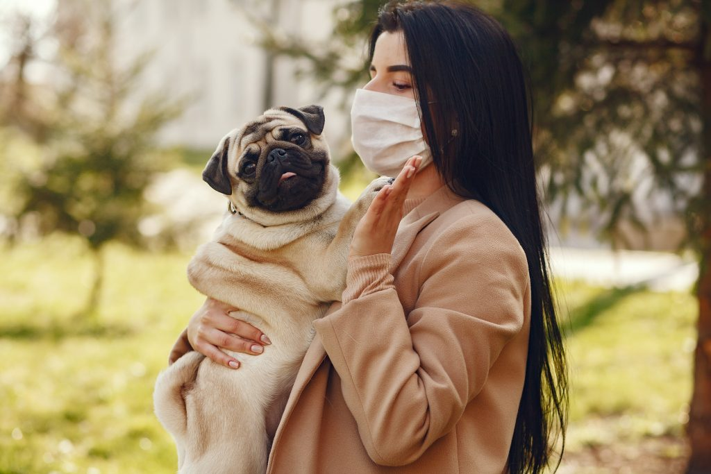 woman wearing facemask and holding dog outdoors
